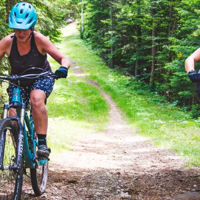 Two mountain bikers climbing a trail at Mt Van Hoevenberg